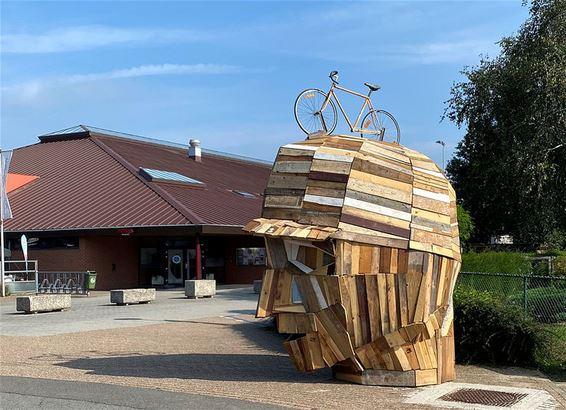 Houten fiets-hoofden bij de school
